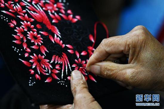 4月2日,在贵州省榕江县卧龙移民小区一刺绣扶贫车间,一名妇女在学习刺绣。