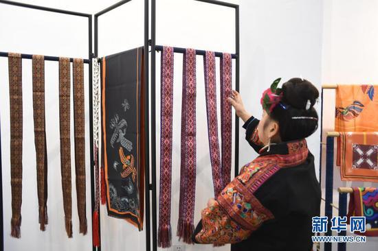 1月21日,在贵州省黔东南苗族侗族自治州施秉县一家刺绣扶贫车间,绣娘检查刺绣质量。