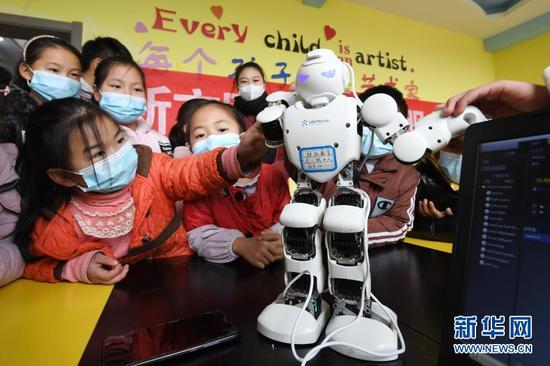 """1月21日,在贵州省毕节市黔西县锦绣街道""""新市民·追梦桥""""服务中心,易地扶贫搬迁安置点的孩子们与机器人""""亲密接触""""。新华社发(邓刚 摄)"""