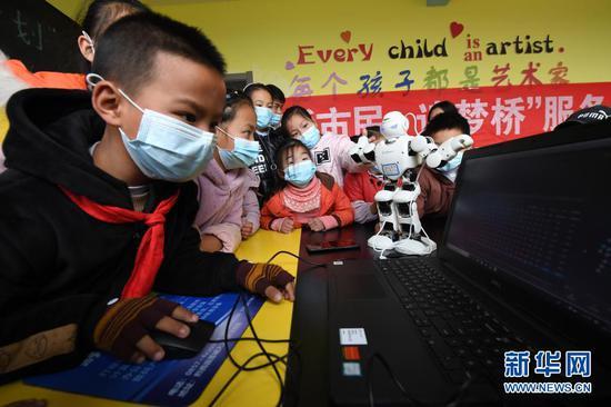 """1月21日,在贵州省毕节市黔西县锦绣街道""""新市民·追梦桥""""服务中心,易地扶贫搬迁安置点的孩子在体验操控机器人。新华社发(邓刚 摄)"""