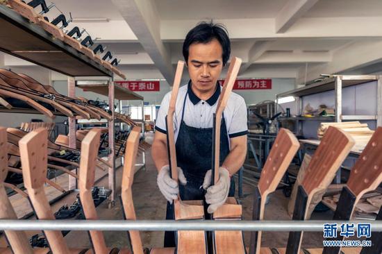 6月24日,工人在吉他生產車間內忙碌。