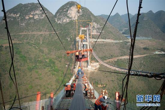 工人在峰林特大桥主塔塔顶施工(3月25日摄)。