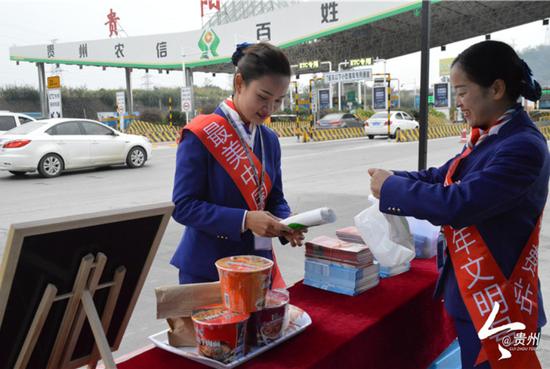 贵阳北收费站常白班班长张贤(左)与同事一起整理便民服务点