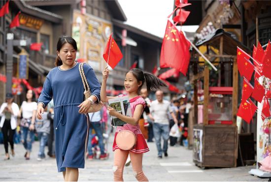 游客在丹寨万达小镇游玩,街头国旗招展,一派祥和喜庆(黄晓海 摄)