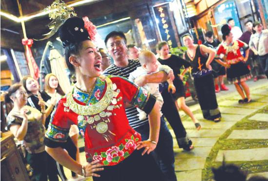 西江苗寨景区,游客兴高采烈地与当地苗家小妹共舞。