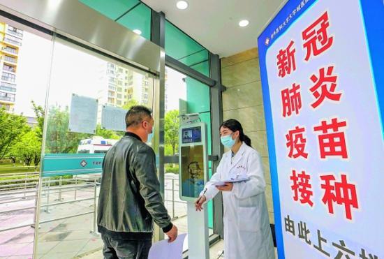 在贵州医科大学大学城医院,前来接种的市民在接受体温监测。