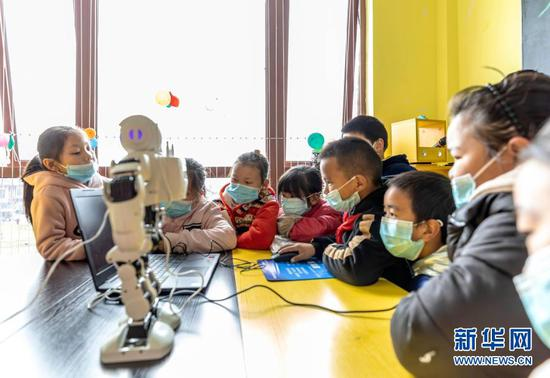 """1月21日,在贵州省毕节市黔西县锦绣街道""""新市民·追梦桥""""服务中心,易地扶贫搬迁安置点儿童体验编程机器人。新华社发(范晖摄)"""