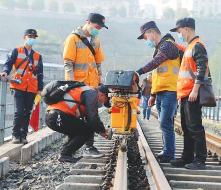 工人推着探伤仪在钢轨上检查