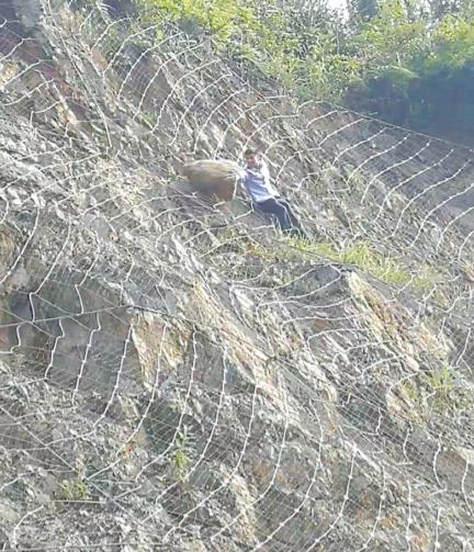 朱宗广爬上边坡观察落石。