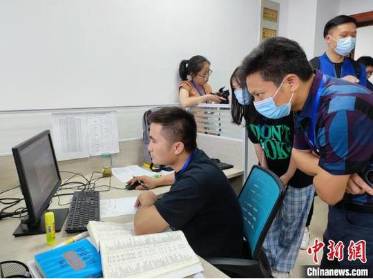 图为考生和家长代表观看高考录取过程。 刘美伶 摄