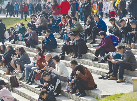 24日,市民们坐在湿地公园的石阶上晒太阳。
