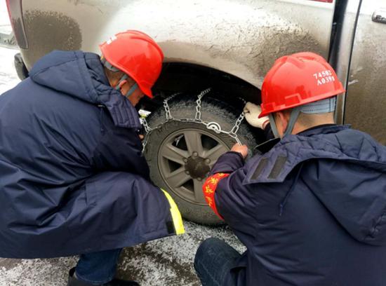 习水供电局党员服务队为抢修车装上防滑链