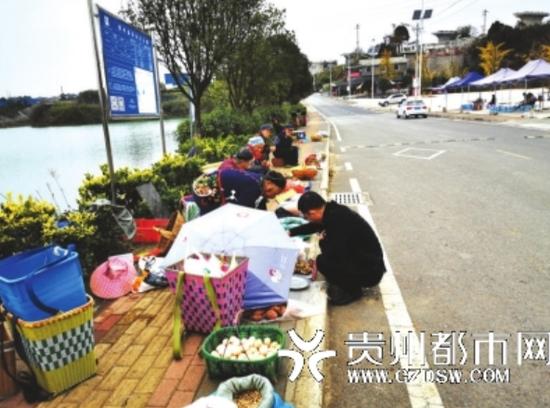 景区中心路边,卖东西的村民比游客还多。