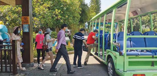 游客按秩序上观光车游览。