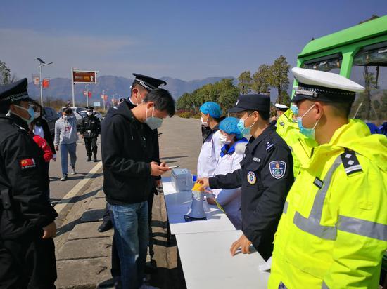2月24日,贵州省兴仁市放马坪景区门口,市公安局山地旅游警察、交通警察、特(巡)警与医护人员对游客进行温测、扫码登记。