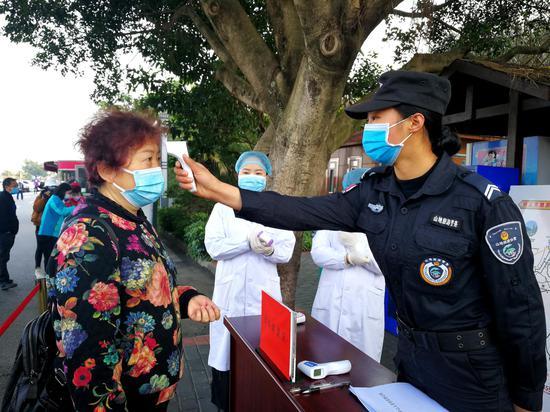 2月24日,贵州省兴义市国家地质公园万峰林景区正式开放迎来首批旅客。兴义市公安局山地旅游警察大队辅警在给游客测温。