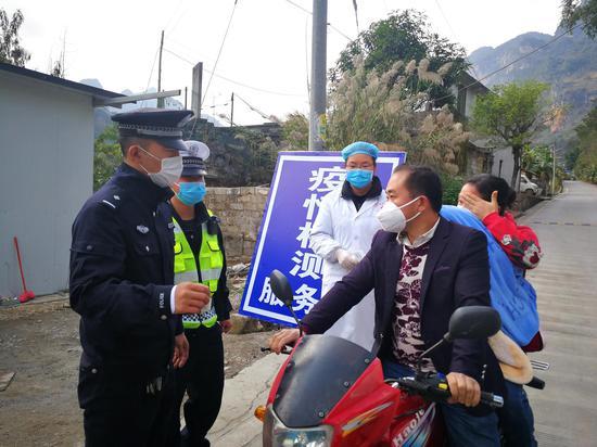 2月5日,贵州省义龙新区德卧镇郎行村,这里与广西隆林县桠杈镇之间隔着一座长桠大桥。德卧派出所民警和镇卫生院的医生正在盘查过往人员和车辆。