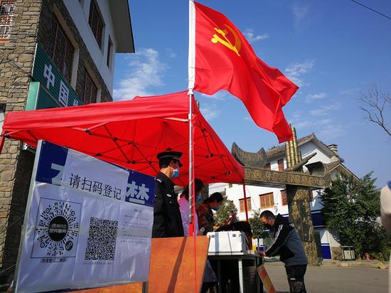 2月24日,贵州省兴仁市薏品田园小镇疫情防控宣传服务点,党旗迎风飘扬,执勤民警、医生和社区干部正在认真履职。