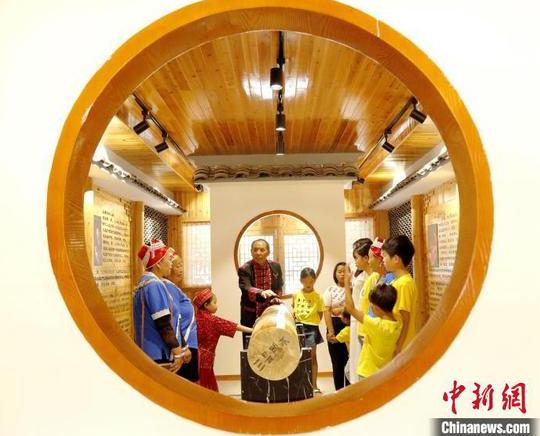 """吳通賢(中)在""""刻道文化展示館""""講述苗族""""刻道""""故事?!》盍?攝"""