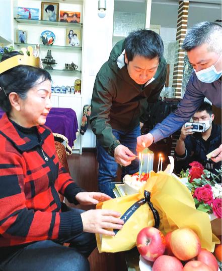 正能量合伙人为朱阿姨切蛋糕。