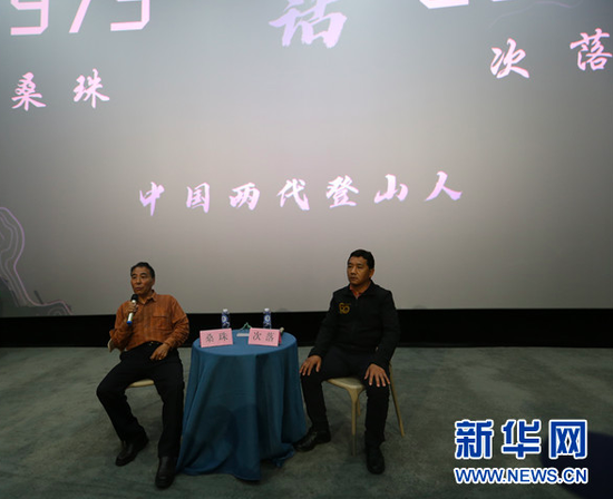 4月24日,两位时隔45年完成珠峰测量任务的登山勇士桑珠(左)、次落(右)在贵阳介绍珠峰登山测量情况,与观众互动交流。新华网 黄勇 摄