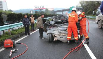 轿车尾部变形严重,消防官兵正在进行破拆,以就出被困男子