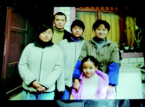 """卓欣、卓欢上初二时,李泽英一家五口在租住房前,拍下了这张""""全家福"""""""