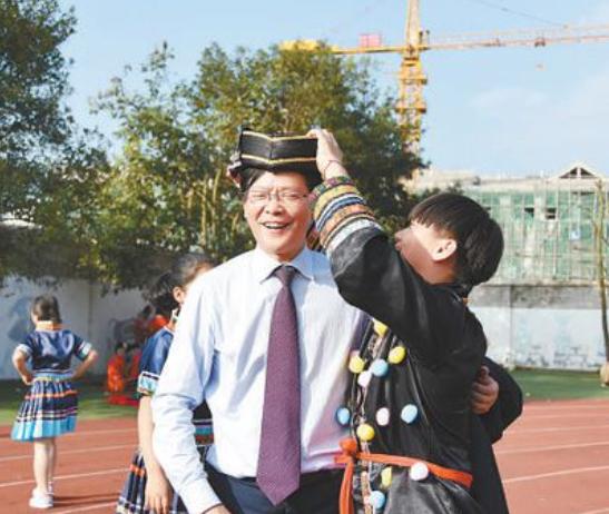 学生给陈立群(左)戴上民族特色帽子。资料照片