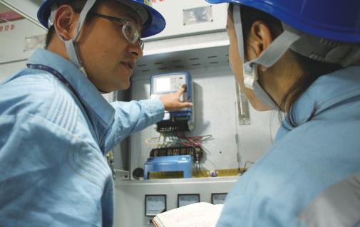 工作人员在居民小区配电房对设备数据进行分析