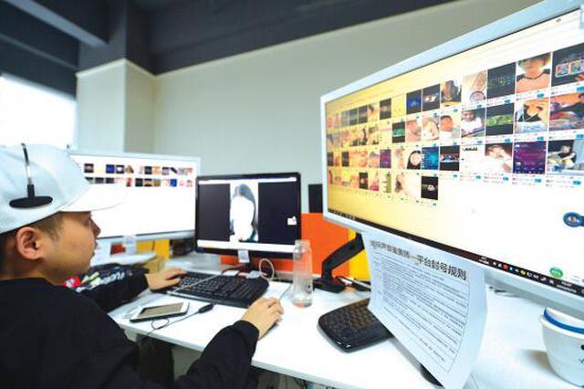 一位声音鉴黄师的工作场景,戴着耳机,听着网络聊天房间内的各种交谈,如果发现涉黄,他会立即进行处理。