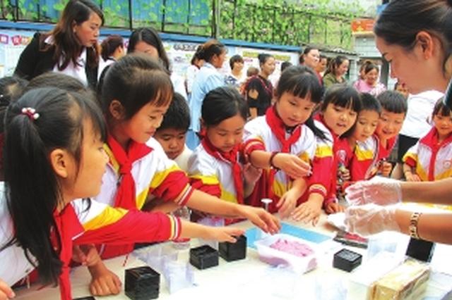 志愿者与小朋友一起制作月饼。