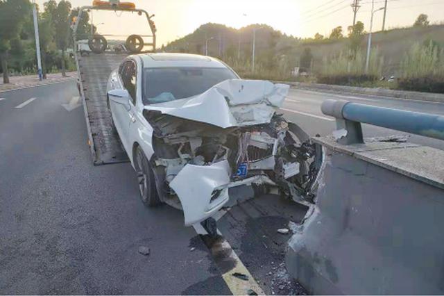 司机低头捡手机 轿车一头撞护栏