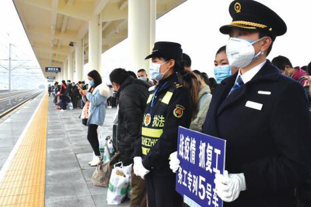 工作人员在站台组织务工人员有序等待。