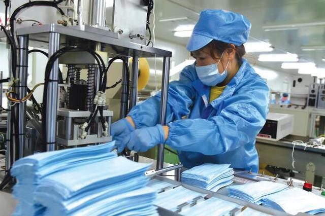 在山西省曲沃县李时珍医药科技有限公司,工人加工口罩。