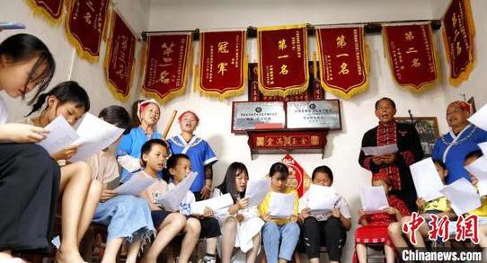 """吳通賢(后右二)給學生們教唱苗族""""刻道歌""""?!》盍?攝"""