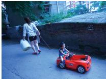 暮色里,一位妈妈拖着玩具车上的孩子前行。