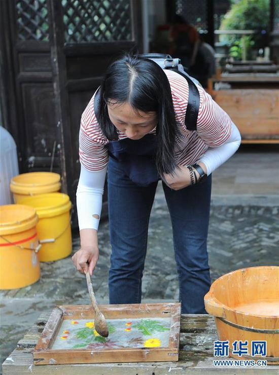 7月2日,游客在丹寨万达小镇体验古法造纸工艺。2017年7月,贵州省丹寨县的丹寨万达小镇对外开放。两年来,丹寨万达小镇游客接待量持续增长,为700余名贫困户提供就业岗位,有力助推了丹寨县的脱贫攻坚工作。新华社记者 欧东衢 摄