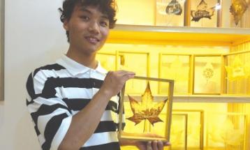 王波展示叶雕作品。