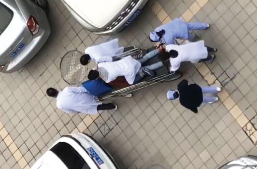 唐章铝跪在平板车上给患者抢救。 视频截图
