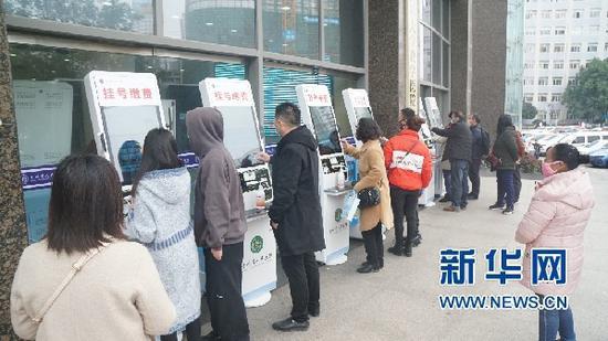 2月24日,人们在贵州省人民医院门诊大楼外的自助机前挂号、缴费。新华网发