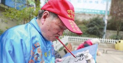 郑宽勤老人的嘴写书法绝活。