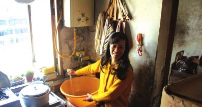 虽然家境困难,但小彭的母亲满脸阳光。