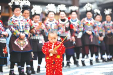 """一名小孩子在""""祭尤节""""中吹奏芦笙。"""