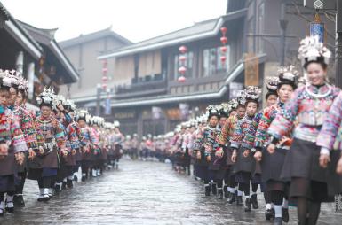 """身着节日盛装的苗族村民参加""""祭尤节""""苗族服饰展示巡游。"""