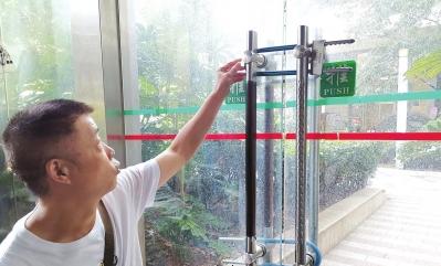健身房的玻璃大门上挂着3把锁。