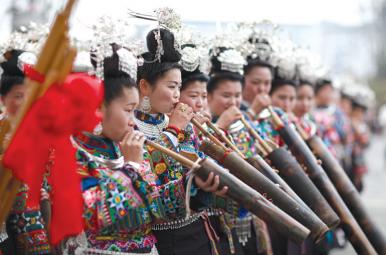 """身着节日盛装的苗族妇女在""""祭尤节""""中吹奏苗族传统乐器""""芒筒""""。"""