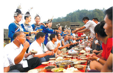 侗家人将烧鱼等摆上长桌宴招待宾朋,一起分享丰收的喜悦。