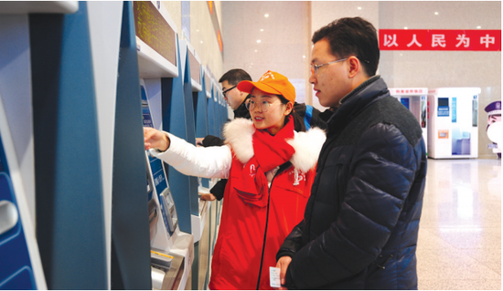 在观山湖打工的杨先生正在志愿者的指导下购买前往铜仁的车票