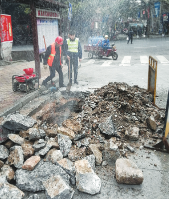 挖开地面找到漏水点,工作人员准备修复