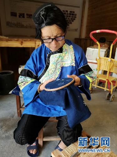 杨老团正在卧龙小区的扶贫车间做刺绣。新华社记者罗羽摄